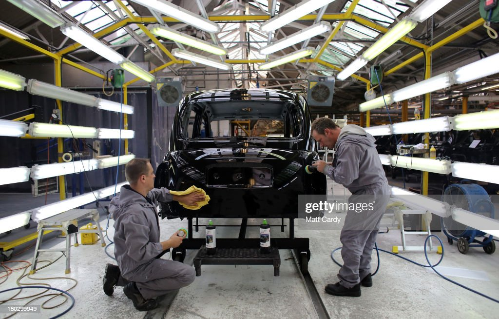 Workers inside the factory of The London Taxi Company polish a TX4 (Euro 5) London Taxi on September 11, 2013 in Coventry, England. The business secretary, Vince Cable, officially restarted the production line of the iconic TX4 black cabs today, six months after the company behind the famous vehicles was rescued by the Chinese company Geely Group.