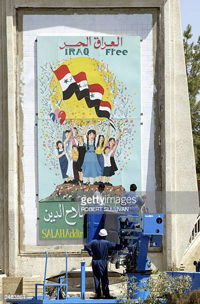 Workers inspect a recently painted mural celebrating freedom 11 September 2003 in Tikrit 175 kilometers north of Baghdad Tikrit the hometown of...