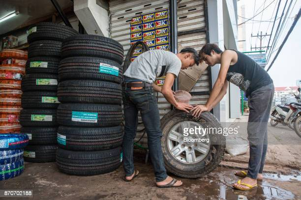 Workers inspect a tire at a store in Vientiane Laos on Thursday Nov 2 2017 Located in the Mekong region Southeast Asia's frontier nations are...