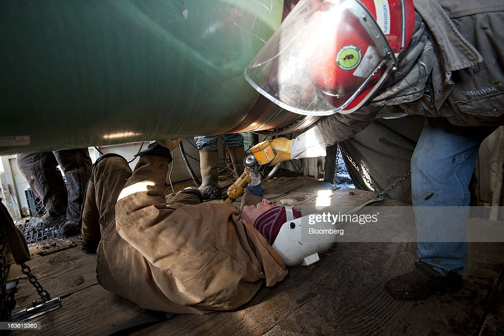 Workers inspect a weld on the joint between two sections of pipe on a Gulf Coast Project pipeline in Atoka, Oklahoma, U.S., on Monday, March 11, 2013. The Gulf Coast Project, a 485-mile crude oil pipeline being constructed by TransCanada Corp., is part of the Keystone XL Pipeline Project and will run from Cushing, Oklahoma to Nederland, Texas. Photographer: Daniel Acker/Bloomberg via Getty Images