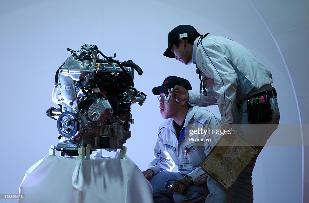 Workers inspect an engine for the Toyota Motor Corp. Aqua hybrid compact car displayed after the line-off ceremony of Toyota Motor East Japan Inc.'s Miyagi Taiwa Plant in Taiwa, Miyagi Prefecture, Japan, on Friday, Dec. 14, 2012. Toyota Motor East Japan Inc. commenced operations at the plant today. Photographer: Tomohiro Ohsumi/Bloomberg via Getty Images