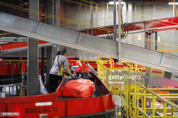 Workers inspect bags of packages as they move down conveyor belts while being sorted at the DHL Worldwide Express hub of Cincinnati/Northern Kentucky...