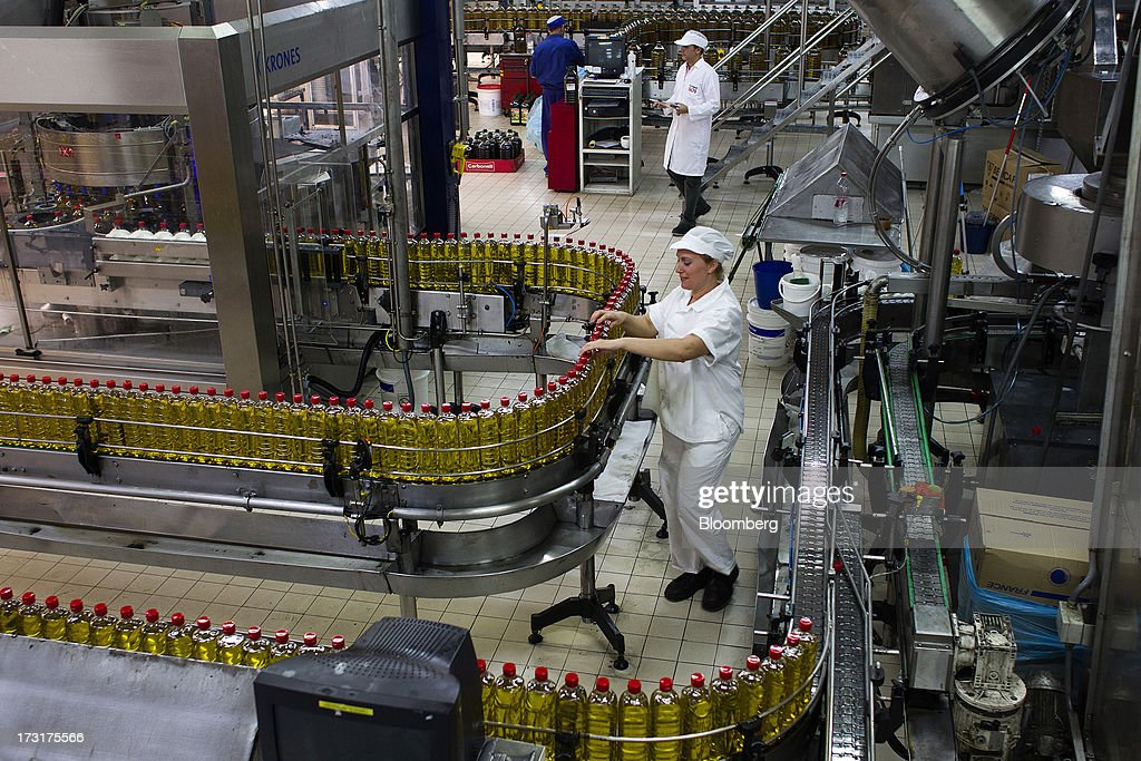 Workers inspect bottles of Spanish olive oil as they move along the production line at the Carbonell SA plant, operated by Deoleo SA, in Alcolea, Spain, on Tuesday, July 9, 2013. JPMorgan was asked to explore sale of more than 30% stake in olive oil company Deoleo, Reuters reports, citing two people close to the deal. Photographer: Angel Navarrete/Bloomberg via Getty Images
