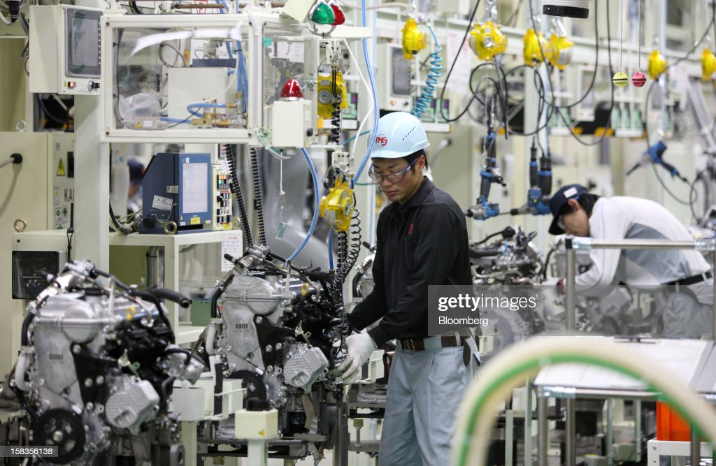 Workers inspect engines for the Toyota Motor Corp. Aqua hybrid compact car on the production line of Toyota Motor East Japan Inc.'s Miyagi Taiwa Plant in Taiwa, Miyagi Prefecture, Japan, on Friday, Dec. 14, 2012. Toyota Motor East Japan Inc. commenced operations at the plant today. Photographer: Tomohiro Ohsumi/Bloomberg via Getty Images