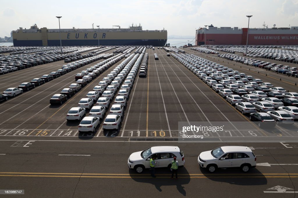 Workers inspect Kia Motors Corp. vehicles bound for export at the port of Pyeongtaek in Pyeongtaek, South Korea, on Monday, Sept. 30, 2013. South Koreas consumer confidence sank to a five-month low in September, even after a rebound in exports fueled the fastest economic growth in two years last quarter. Photographer: SeongJoon Cho/Bloomberg via Getty Images