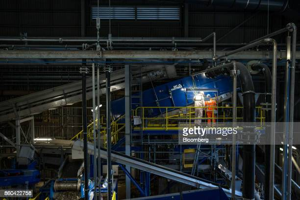 Workers inspect machinery in the sorting hall at the Renescience waste energy plant operated by Dong Energy A/S in Northwich UK on Thursday Oct 5...