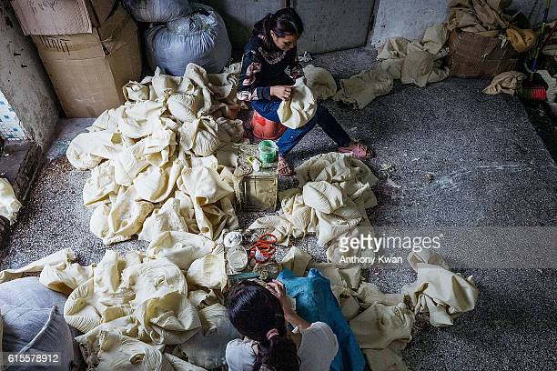 Workers inspect newlymade masks of Donald Trump at the Shenzhen Lanbingcai Latex Crafts Factory on October 18 2016 in Shenzhen China Shenzhen...