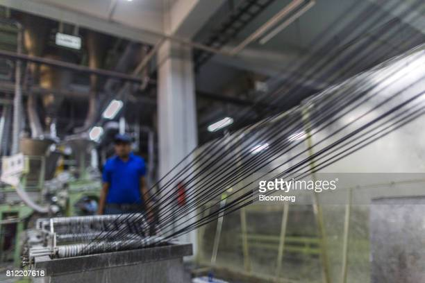 Workers inspect plastic threads passing through an extruder that makes plastic pellets at Dainichi Color India Pvt's factory in the Rajasthan State...