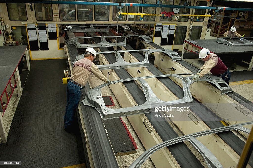 Workers inspect sheet auto metal components : Stock Photo