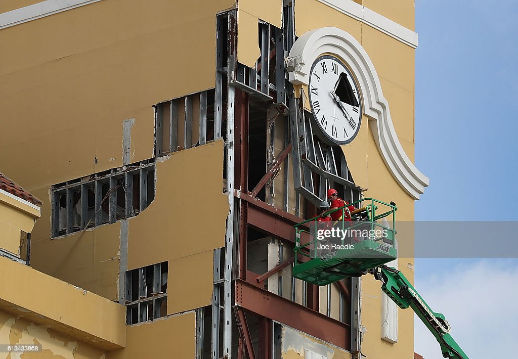 Workers inspect the damage to a building from the high winds of Hurricane Matthew on October 8 2016 in Daytona Florida Across the Southeast over 14...