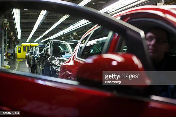 Workers inspect the interior of an Opel Astra automobile during quality control checks at the end of the production line at General Motors Co's Adam...