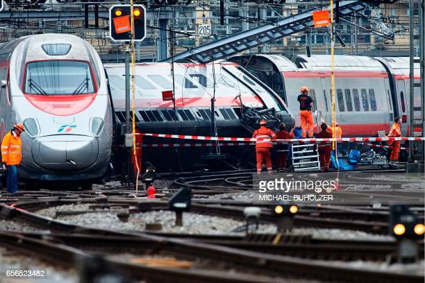 Workers inspect the site of a train crash at the train station of Lucerne where a Eurocity train of Trenitalia derailed on March 22 2017 / AFP PHOTO...