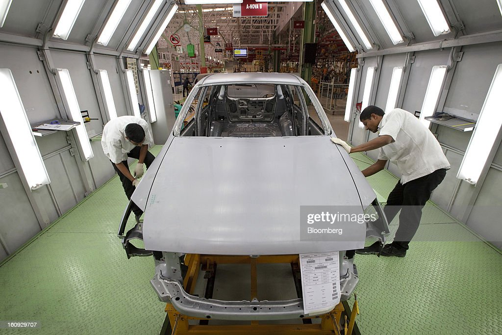 Workers inspect vehicle parts on the assembly line for the Mahindra & Mahindra Ltd. Rexton sport utility vehicle (SUV) at the company's factory in Chakan, Maharashtra, India, on Wednesday, Feb. 6, 2013. Mahindra & Mahindra is scheduled to announce third-quarter earnings today. Photographer: Kuni Takahashi/Bloomberg via Getty Images