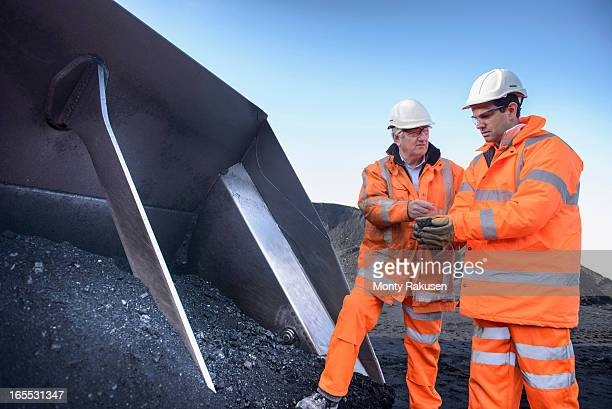 Workers inspecting coal at surface coal mine