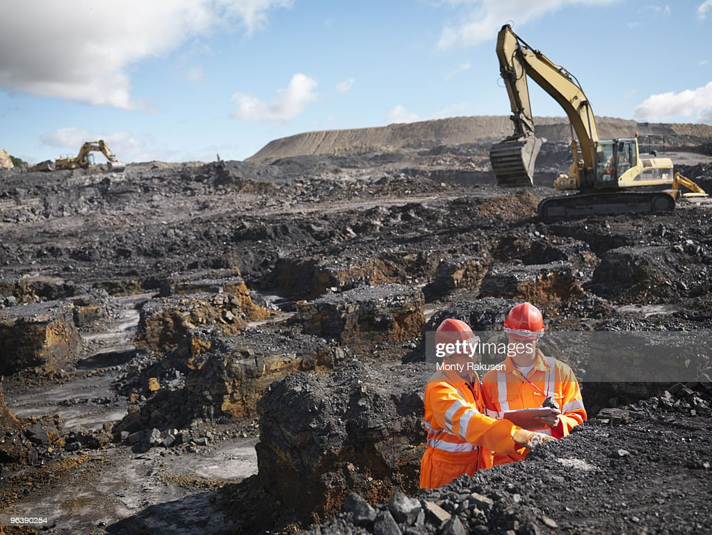 Workers Inspecting Coal In Mine