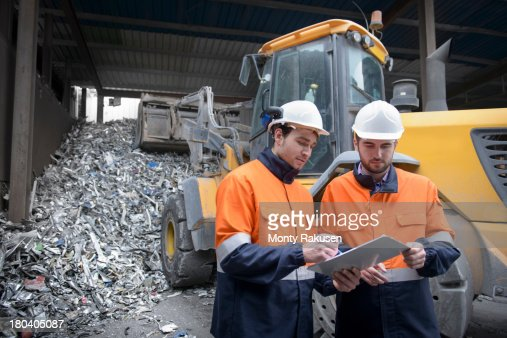 Workers inspecting paperwork in  recycling plant in front of scrap aluminium