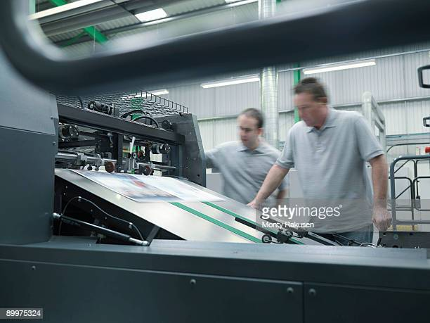 Workers Inspecting Printer