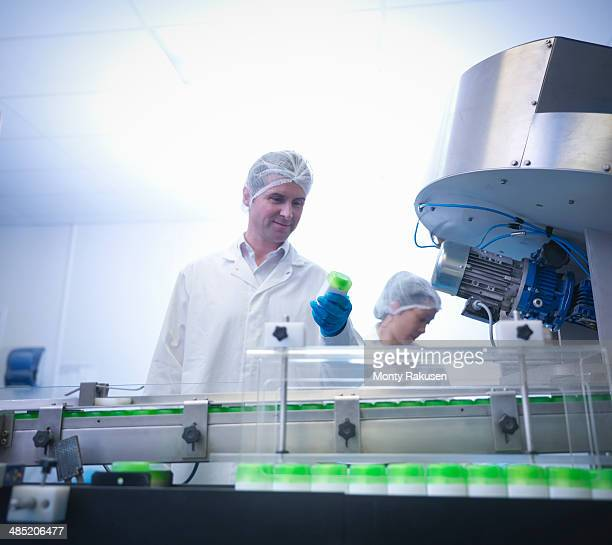 Workers inspecting products on production line in pharmaceutical factory