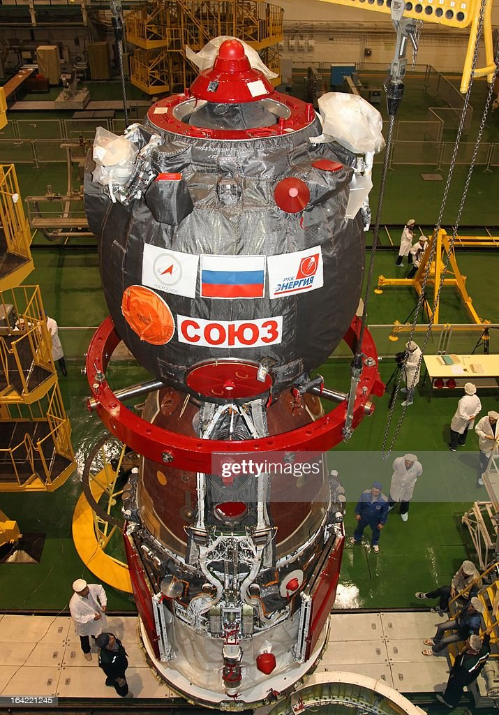 Workers inspects a Russian Soyuz TMA-08M spacecraft in assembling department in the Russian leased Kazakhstan's Baikonur cosmodrome on March 20, 2013. Russian cosmonauts, Pavel Vinogradov, Alexander Misurkin, and US astronaut Christopher Cassidy are scheduled to blast off in the Soyuz spacecraft to the International Space Station (ISS) from the Baikonur cosmodrome on March 28.