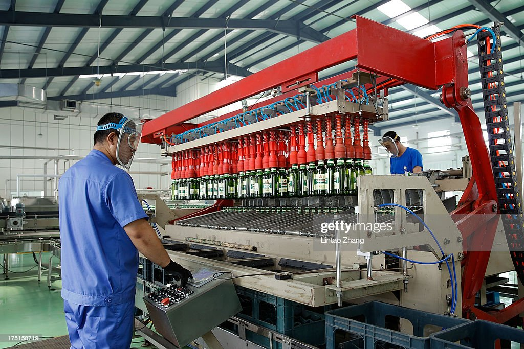 Workers inspects bottles of beer moving along a production line at the Jinzhu Manjiang beer factory on August 1, 2013 in Fujin, Heilongjiang Province, China. Recent significant sustained high temperatures in China are expected to push beer industry volume and revenue growth up significantly.