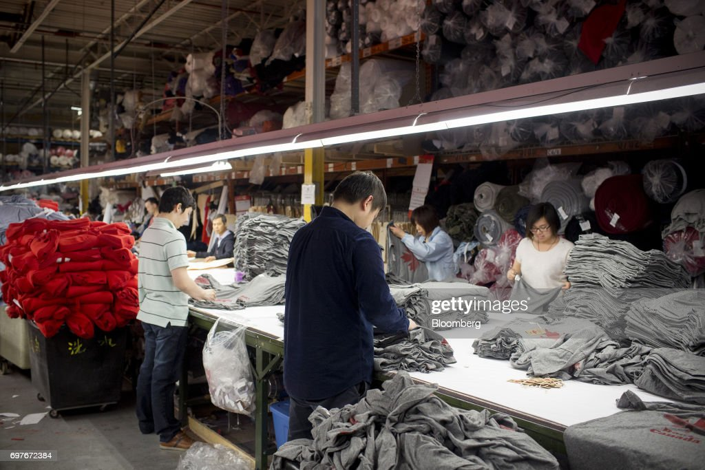 Workers inspects clothing at the WS & Co. production facility in Toronto, Ontario, Canada, on Friday, June 9, 2017. Canada Day celebrates the anniversary of the creation of the Canadian Federation through the North America Act on July 1. Photographer: Brent Lewin/Bloomberg via Getty Images