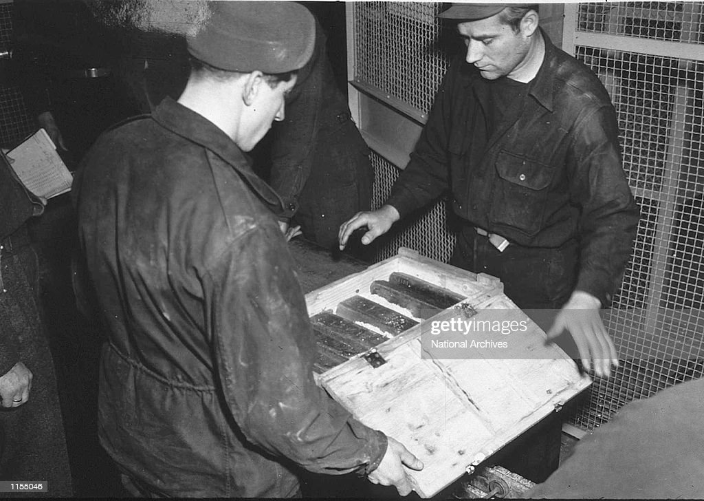 Workers inspects gold bars taken from jews by the Nazi's and stashed in the Heilbron Salt Mines May 3 1945 in Germany The treasures were uncovered by...