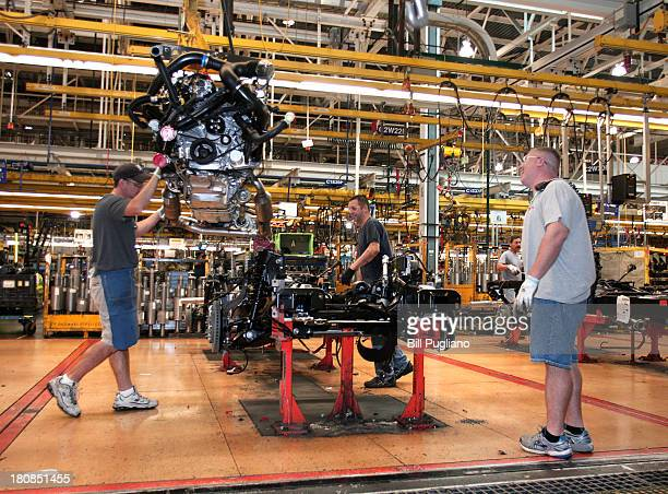 Workers install a Ford EcoBoost engine into a 2014 F150 truck chassis on the assembly line at Ford's Dearborn Truck Plant September 16 2013 in...