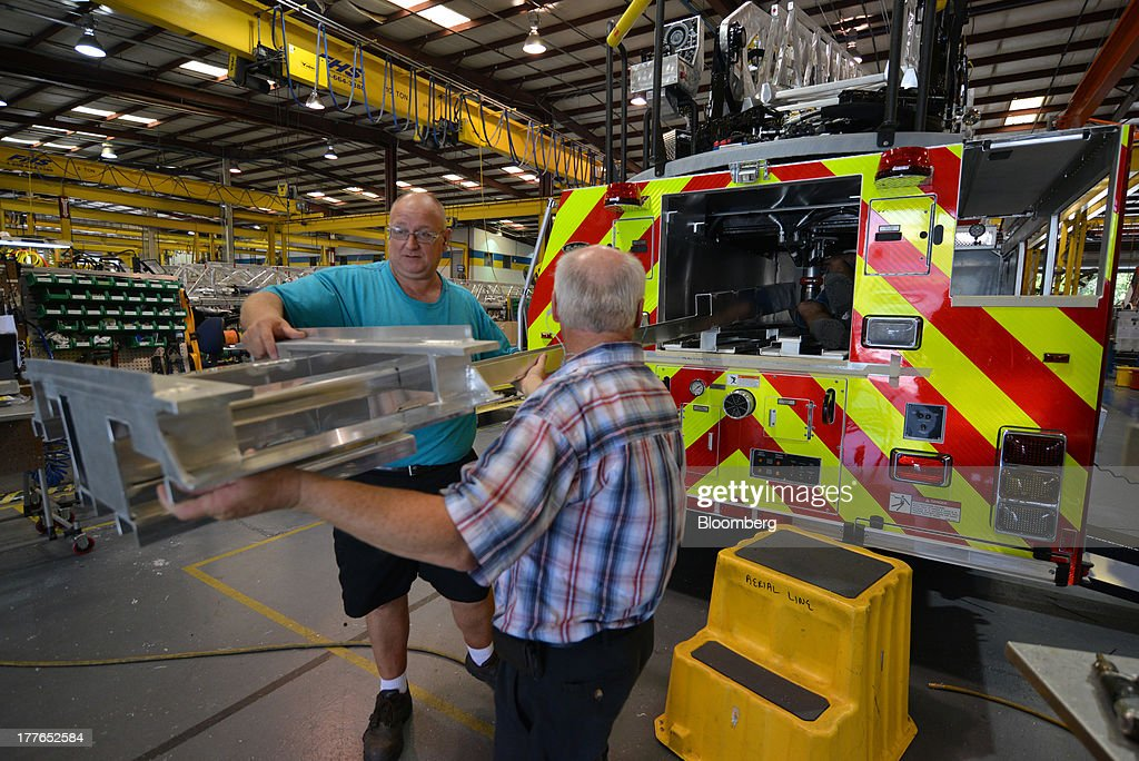 Workers install a ladder rack into an E-ONE Inc. aerial truck at the E-ONE factory, on Tuesday, Aug. 20, 2013, in Ocala, Florida, U.S. The U.S. Census Bureau is scheduled to release durable goods figures on Aug. 26. Photographer: Mark Elias/Bloomberg via Getty Images