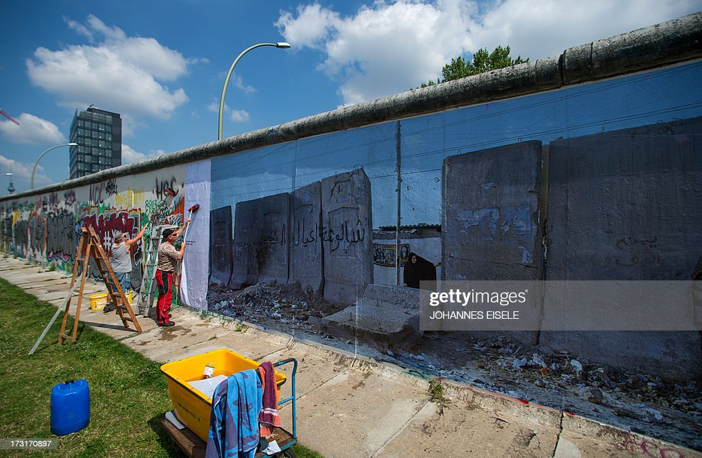 Workers install a panorama picture made by German photographer Kai Wiedenhoefer, showing a wall at the West Bank, as preparations are under way on July 9, 2013 in Berlin for Wiedenhoefer's 'Wall on Wall' exhibition at the East Side Gallery, the longest stretch remaining of the Berlin Wall. The 'Wall on Wall' project by the award-winning artist features 36 panoramas taken in Northern Ireland, Iraq, Cyprus, the West Bank, Morocco, South Korea and the border zone between the United States and Mexico. The exhibition is running until September 13, 2013. AFP PHOTO / JOHANNES EISELE
