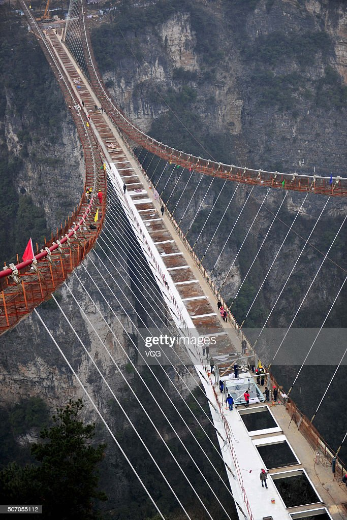 Workers install a piece of glass on a suspension bridge, approximately 300 metres above ground, at The Grand Canyon of Zhangjiajie on January 27, 2016 in Zhangjiajie, China. The glass-bottomed bridge, 430 metres in length and 6 metres in width, is expected to open in May this year.