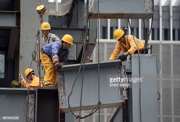 Workers install a section of a steel beam on a construction site in Beijing on September 9 2015 China's government says the world's second largest...