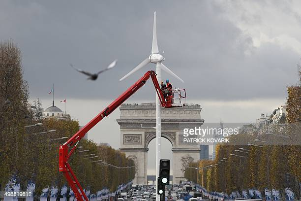 Workers install a wind turbine on the ChampsElysees avenue on November 26 2015 in Paris ahead of the 21st Session of the Conference of the Parties to...