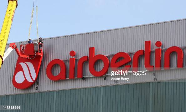 Workers install an Air Berlin logo at the company's hangar at Berlin Brandenburg Airport on May 4 2012 in Schoenefeld near Berlin Germany The new...