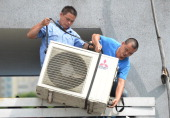 Workers install an airconditioning unit in a food stall in Shanghai on July 2 2013 The Shanghai Meteorological Bureau forecast a heat wave as...