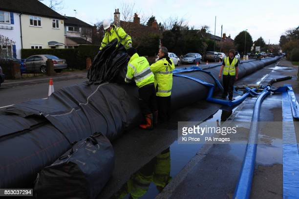 Workers install an aqua dam to protect homes from expected floodwater in Chertsey Surrey as two people have died and tens of thousands of homes are...