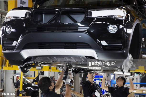 Workers install an exhaust pipe on a BMWX5 xDrive40e M Sport plugin hybrid vehicle at the BMW AG assembly plant in Amata Rayong province Thailand on...