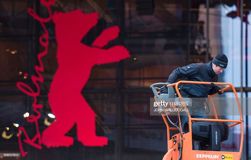 Workers install audio equipment in front of the Berlinale Film Festival's main venue, the Berlinale Palast, in Berlin on February 9, 2016. Movies starring Colin Firth, Kirsten Dunst and Emma Thompson will vie for gold at the 66th Berlin film festival starting February 11, with Meryl Streep as jury president and a spotlight on Europe's refugee crisis. / AFP / John MACDOUGALL