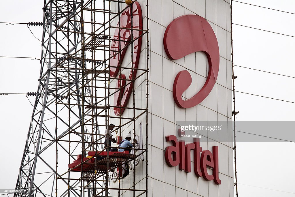 Workers install Bharti Airtel Ltd. signage while standing on scaffolding at a business park in Gurgaon, India, on Wednesday, March 26, 2014. Indian stocks rose, sending the benchmark index to a record, after the rupee rose to an eight-month high and sovereign bonds gained on speculation the worlds largest democracy will elect a government capable of reviving economic growth. Photographer: Kuni Takahashi/Bloomberg via Getty Images