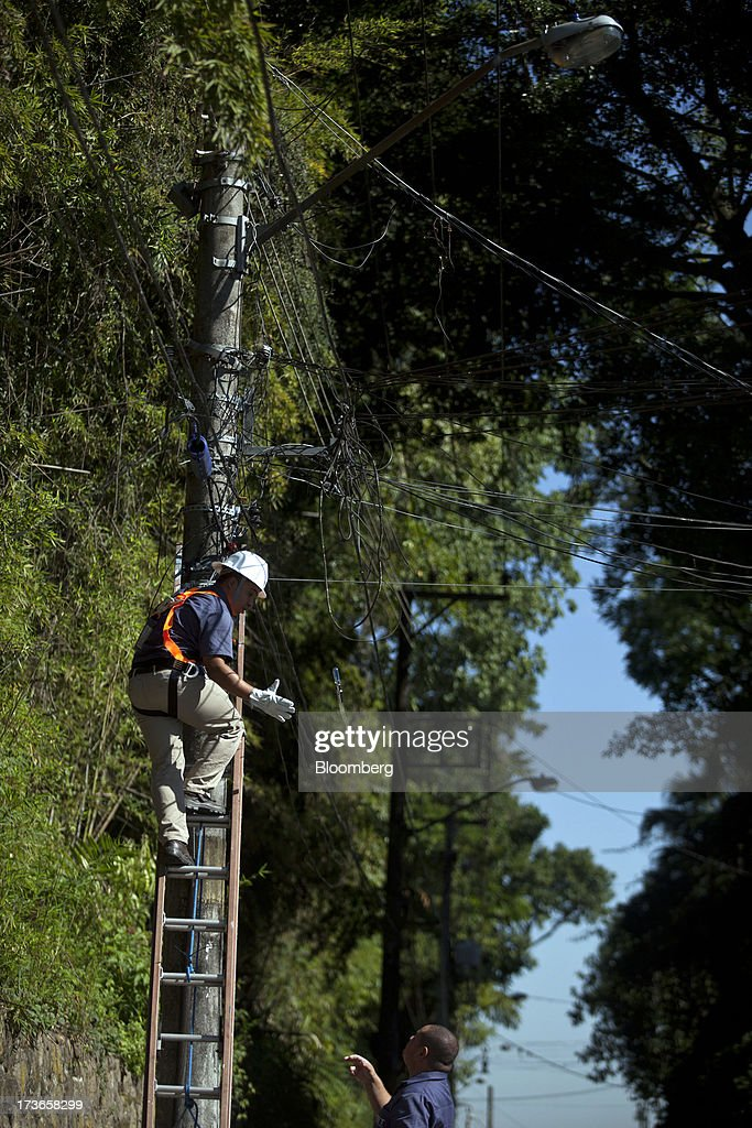 Workers install cables on an electricity pole in the Santa Teresa neighborhood of Rio de Janeiro, Brazil, on Monday, July 15, 2013. Energy developers in Brazil will bid for contracts to sell electricity Dec. 13 from plants due to go into operation in five years, including a 700-megawatt hydropower project in the Amazon. Photographer: Dado Galdieri/Bloomberg via Getty Images