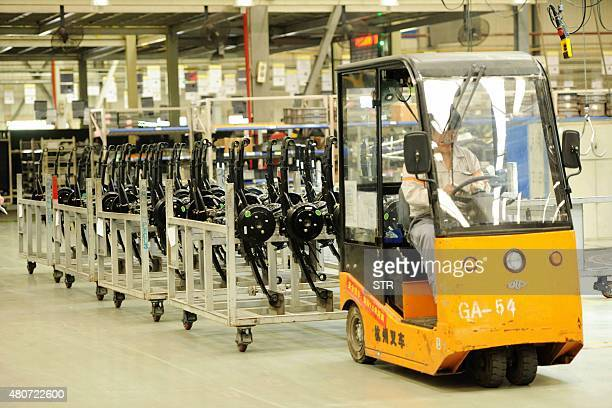 Workers install car parts at their assembly line in a factory in Qingdao east China's Shandong province on July 15 2015 China's GDP expanded 70...