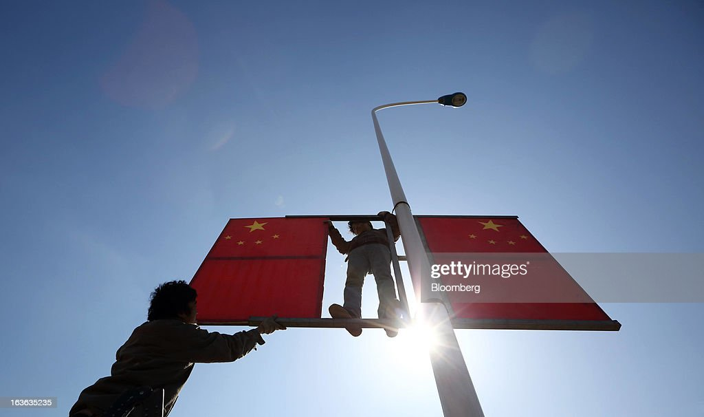 Workers install Chinese flags on a lamp post on a street in Tianjin, China, on Wednesday, March 13, 2013. China's National People's Congress, or the legislature, will select the nation's president and vice president on March 14. Photographer: Tomohiro Ohsumi/Bloomberg via Getty Images