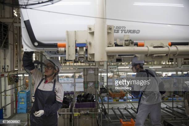 Workers install components into a Nissan Motor Co Navara pickup truck on an assembly line at the company's plant in Samut Prakan Thailand on Tuesday...