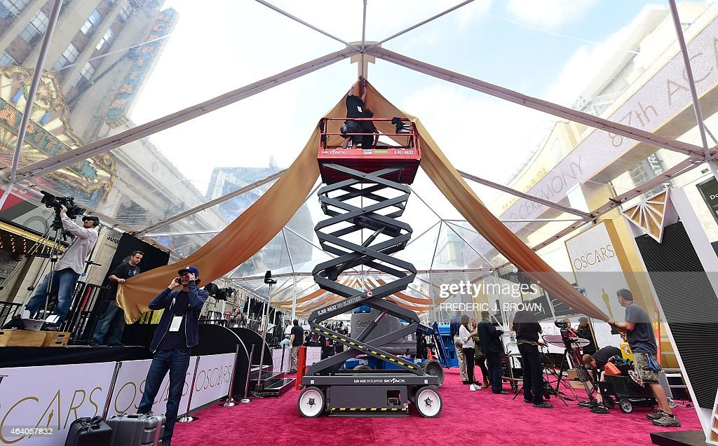 Workers install drapes within the tarp put in place covering the red carpet in case of rain as final preparations take place on February 21 2015 one...