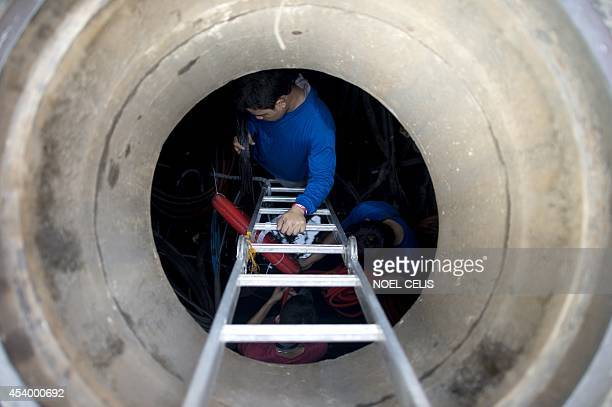 Workers install fiber optics inside a manhole to improve telephone and internet services in Manila on August 23 2014 The Philippines announced in...
