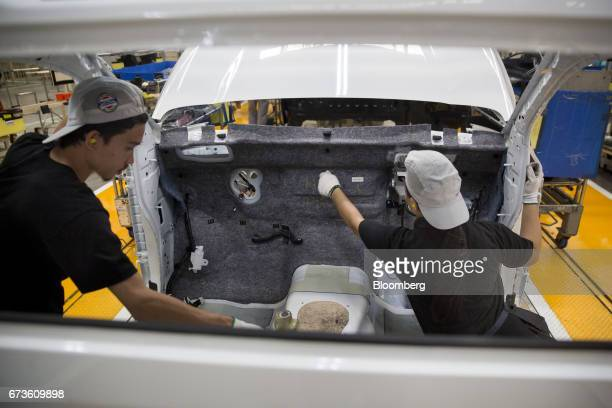 Workers install interior components in a Nissan Motor Co Navara pickup truck on an assembly line at the company's plant in Samut Prakan Thailand on...
