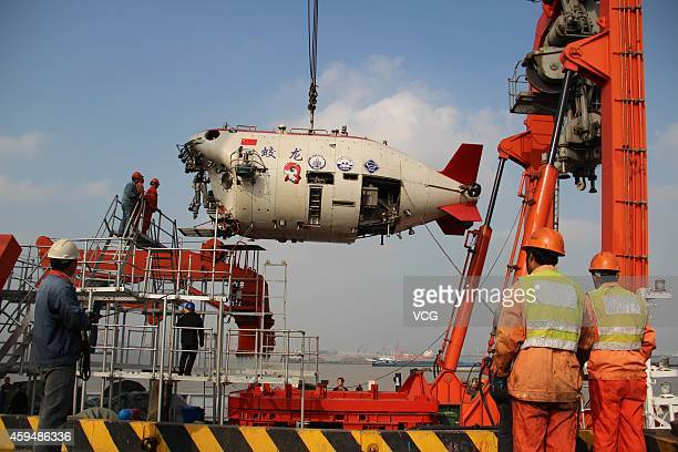 Workers install Jiaolong China's manned deepsea research submersible onto its carrier Xiangyanghong 09 at Jiangyin Sunan International Container...
