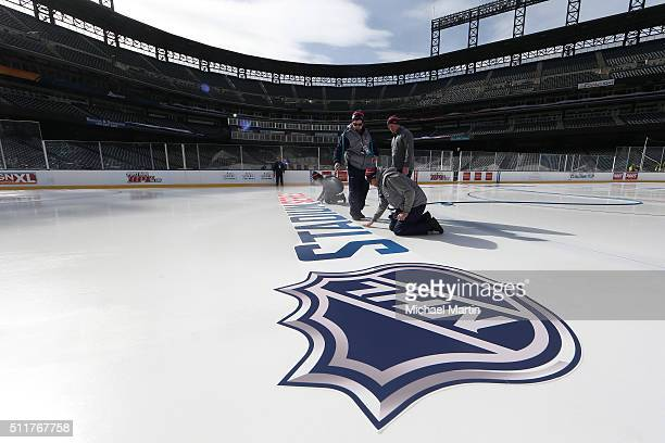 Workers install logos into the ice as part of the 2016 Coors Light NHL Stadium Series at Coors Field on February 22 2016 in Denver Colorado