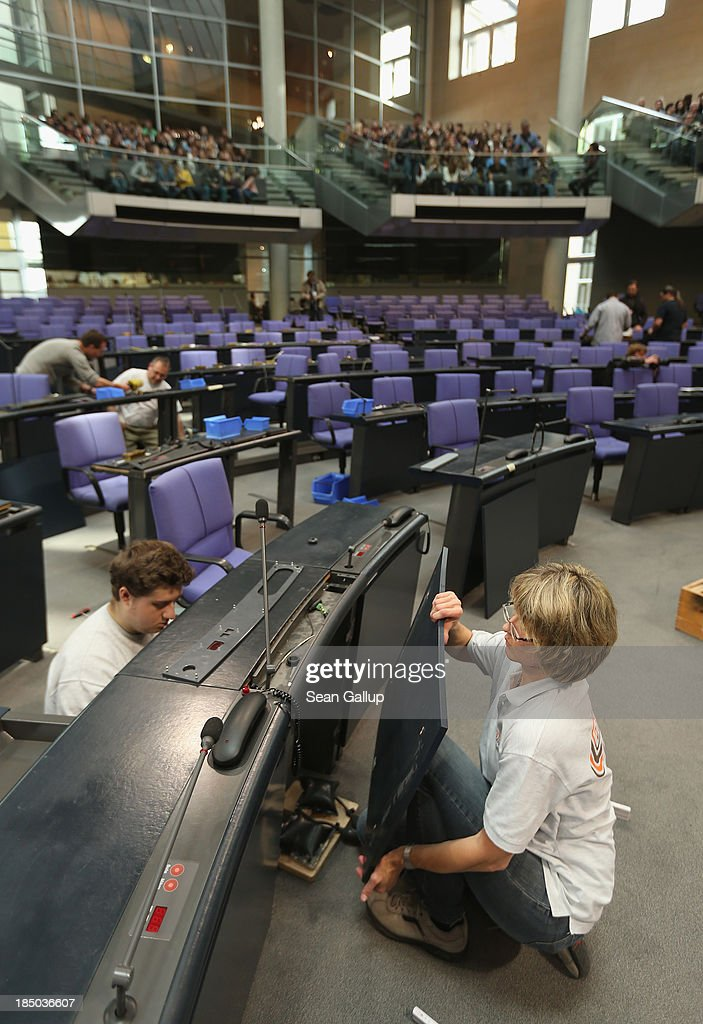 Workers install new desks and chairs in the plenary hall of the Bundestag on October 17, 2013 in Berlin, Germany. Workers installed new chairs and rearranged seating in order to accomodate the new constellation of party factions as well as the slightly higher number of parliamentarians voted in for the 18th legislative period following recent German elections. The new Bundestag will convene for th first time on October 22.
