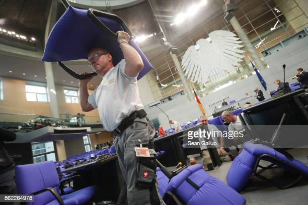 Workers install new seats and working spaces for parliamentarians in the Bundestag at the Reichstag on October 17 2017 in Berlin Germany Following...