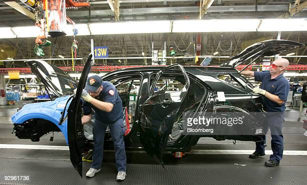 Workers install parts onto a GMC Terrain vehicle at the CAMI Automotive Inc plant assembly line in Ingersoll Ontario Canada on Monday Nov 9 2009 CAMI...
